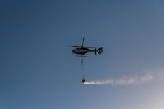 Firefighting helicopter. ROME – AUGUST 23: Firefighting helicopter carrying bucket containing water from Mediterranean Sea to put out fires on scrubland on Stock Photography