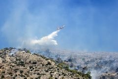 Firefighting plane extinguishes a fire on the hillside . Greece. stock images