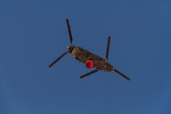Firefighting twin rotor helicopter. ROME – AUGUST 23: Firefighting twin rotor helicopter carrying bucket containing water from Mediterranean Sea to put out Royalty Free Stock Image
