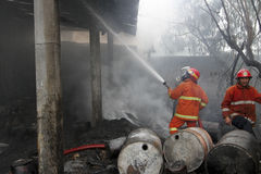 Firefigthers. Firefighter extinguish a burning garage in the city of Solo, Central Java, Indonesia Royalty Free Stock Photos