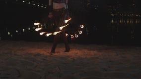 Firegirl performing dance steps holding fire fans stock video