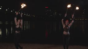 Firegirls performing fireshow with lit torches stock video footage