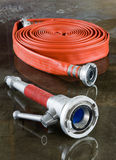 Firehose and nozzle. A rolled up firehose and a nozzle on the wet floor in a firestation used by firefighters royalty free stock image