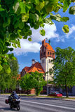 Firehouse building in Riga. On a background of green trees and passing by on the street biker Stock Image