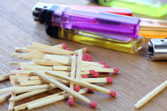 Firemakers. Lots of colorful lighters and matches pile on a wooden table stock photography