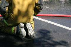 Fireman. Sitting down by red hose, view of his back royalty free stock photo