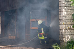 Fireman. Fighting a fire in a burning building stock images
