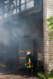 Fireman. Fighting a fire in a burning building stock photography
