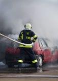 Fireman. Fighting a car fire Stock Photos