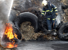Fireman. A fireman estinguishing fire of tyres Stock Image