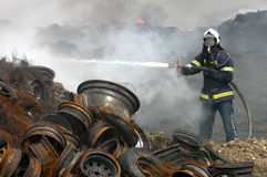 Fireman. A fireman estinguishing fire of tyres Stock Photography
