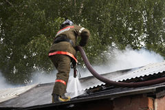 Fireman. The fireman in the form with hose extinguish a fire burning warehouse Stock Photos