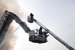 Fireman. A fireman fighting a fire from ladder Royalty Free Stock Image