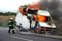 Fireman in action. Fireman putting out van that is burning Stock Images