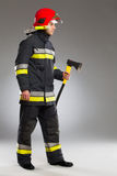 Fireman with axe, side view. Royalty Free Stock Images