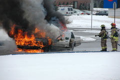 Fireman battle car fire in winter Royalty Free Stock Photos