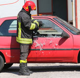 Fireman while breaking the glass of a car with a special equipme Stock Photography