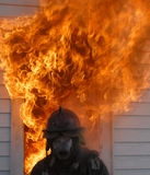 Fireman in breathing apparatus. A fireman in breathing apparatus stands in front of flames exploding out of a burning building royalty free stock image
