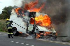 Fireman and Burning Motor Car stock photos