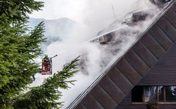Fireman and burning roof Royalty Free Stock Photos