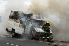 Fireman and Burning Vehicle stock photos