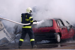 Fireman at car fire. Fireman fighting a car fire after a road accident royalty free stock photography