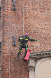 Fireman climbing with ropes and climbing equipment on an old bui. Fireman with ropes and climbing equipment on an old building to monitoring the stability after Stock Photos
