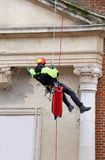 Fireman climbing with ropes and climbing equipment to monitoring. Fireman climbing with ropes and climbing equipment on an old building to checking the stability Stock Image
