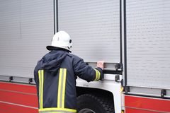 The fireman closes the fire engine blocks. The fireman closes the units with the equipment on board the fire engine Stock Photos