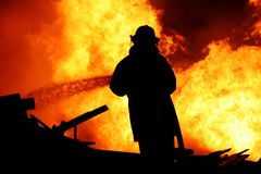 Fireman controlling a huge fire. Fireman fighting a raging fire with huge flames of burning timber Royalty Free Stock Images