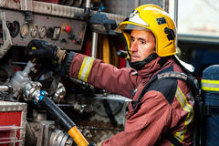 Fireman controlling water pressure at truck. Stock Photos