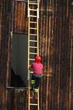 Fireman during a demonstration of using the ladder to reach the. Firefighter during a demonstration of using the ladder to reach the high floors of the Royalty Free Stock Photography