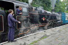 Coupled up - 80080 to old BR carriages. Fireman and driver wait on the 80080 tank engine at East Lancs railway. Tender first.The British Railways Standard Class stock images