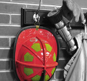 Fireman Equipment. A fireman's hat hose glove and coat hung on a brick wall with the red and yellow helmet accented Stock Images