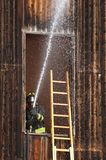 Fireman extinguish a fire with a hose Royalty Free Stock Photos