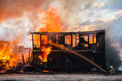 Fireman extinguishes a burning house Royalty Free Stock Images