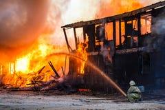 Fireman extinguishes a burning house Royalty Free Stock Photos