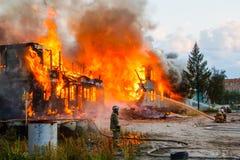 Fireman extinguishes a burning house Stock Photography
