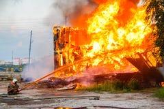Fireman extinguishes a burning house Stock Photos
