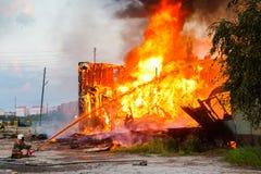 Fireman extinguishes a burning house Stock Image