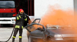 Fireman extinguishes the fire after car accident 2 Royalty Free Stock Photos