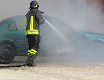 Fireman extinguishes the fire of a car Royalty Free Stock Photos