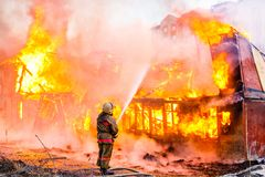 Fireman extinguishes a fire Stock Photos