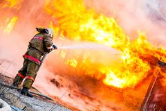 Fireman extinguishes a fire. In an old wooden house Royalty Free Stock Photos
