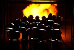 Fireman fighting fire. Firemen approaching a fire wearing bunker gear Royalty Free Stock Photos