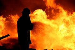 Fireman fighting a fire. Fireman fighting a raging fire with huge flames of burning timber Royalty Free Stock Photo