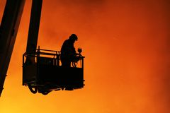 Fireman and fire. Fireman on a crane with a red glow from fire as a background Stock Image