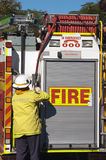 Fireman and Fire Engine. An Australian fire engine with fireman fixing the hose to the truck Royalty Free Stock Images