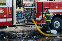 Fireman at fire engine. Kent, WA, USA November 14, 2016: A yellow fire hose attached to pumping station of fire engine and a fireman for Kent Fire Dept Stock Photo
