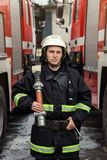 Fireman firefighter in action standing  near a firetruck. Emer. Gency safety . Protection, rescue from danger Stock Photos